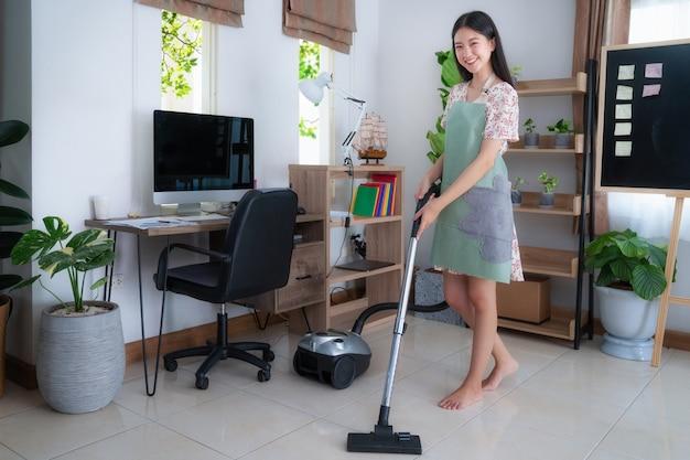 Pavimento aspirapolvere della giovane donna asiatica a casa