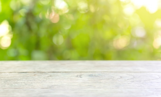 Pavimento di legno con gli alberi vaghi del fondo del parco naturale e la stagione estiva, montaggio dell'esposizione del prodotto