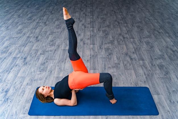 Pavimento di yoga di pratica della donna attraente sul di legno grigio. femmina che indossa abbigliamento sportivo nero e arancione che giace in posizione postura tirando la gamba verso l'alto.