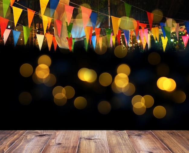 Pavimento in legno e bandiere colorate sopra bokeh per la decorazione del partito di notte