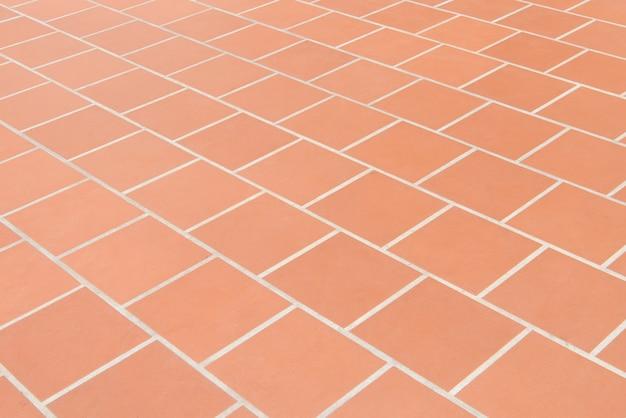 Pavimento piastrellato di ceramica fondo rosso di struttura del muro di mattoni.