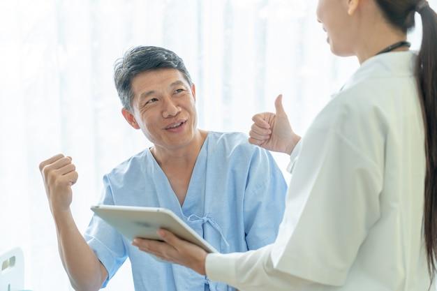 Paziente anziano asiatico sul letto di ospedale che discute con il medico femminile