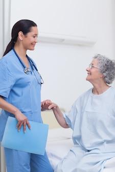 Paziente anziano che tiene la mano di un'infermiera