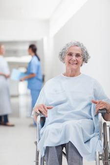 Paziente anziano in una sedia a rotelle in un corridoio