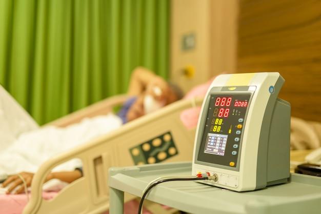 Paziente anziano nel letto di ospedale che controlla assistenza sanitaria di pressione sanguigna.