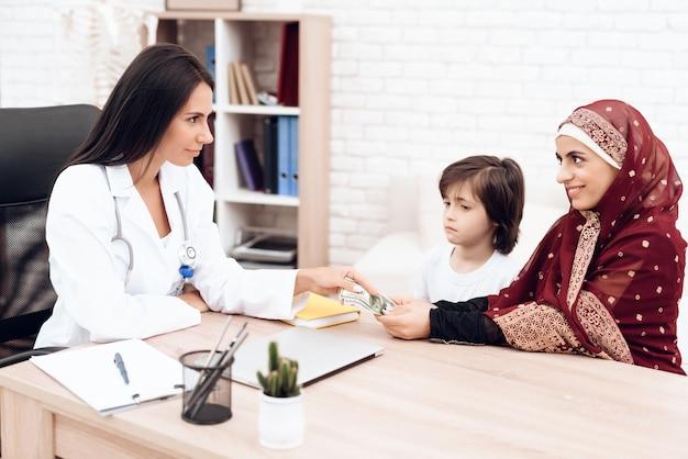 Paziente arabo sorridente che dà soldi per medico