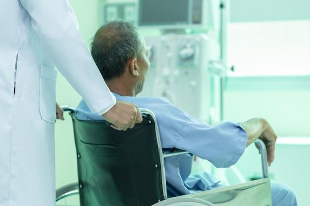 Paziente asiatico in sedia a rotelle che si siede nel corridoio dell'ospedale con medico maschio asiatico.
