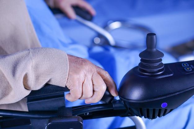 Paziente asiatico o anziano della donna della signora anziana sulla sedia a rotelle elettrica all'ospedale di cura.