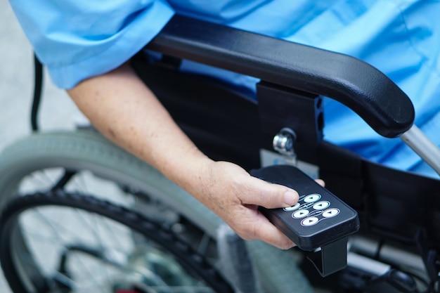 Paziente asiatico o anziano della donna della signora anziana sulla sedia a rotelle elettrica all'ospedale di cura