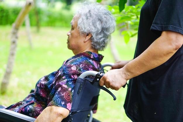 Paziente asiatico o anziano della donna della signora anziana sulla sedia a rotelle in parco.