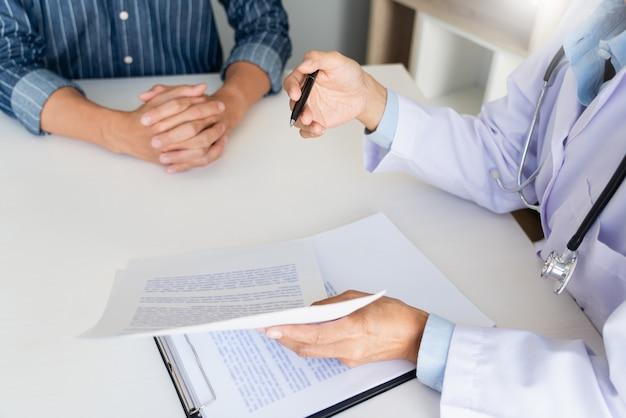 Paziente che ascolta attentamente un dottore maschio che spiega i sintomi del paziente o fa una domanda mentre discutono insieme delle scartoffie in una consultazione