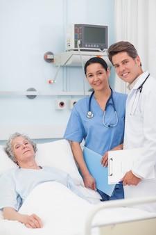 Paziente con il suo medico e infermiere guardando la fotocamera