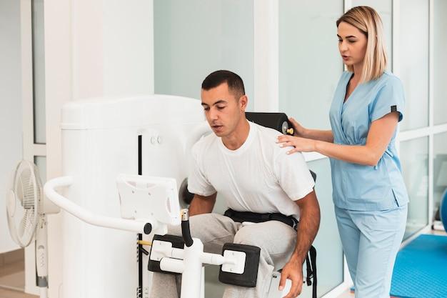 Paziente d'aiuto di medico femminile con un esercizio
