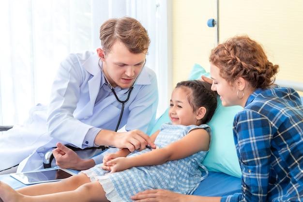Paziente d'esame della bambina dell'uomo del pediatra (medico) facendo uso di uno stetoscopio sull'ospedale della camera da letto.