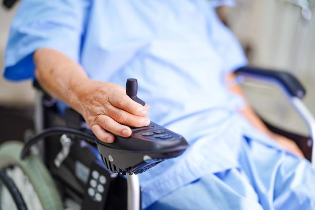 Paziente donna asiatica senior sulla sedia a rotelle elettrica.