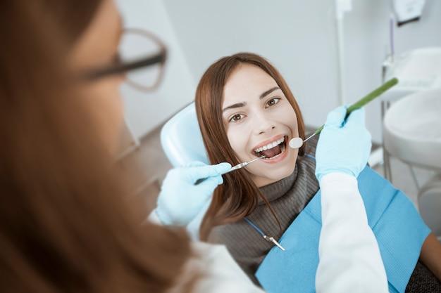Paziente femminile che si siede in una sedia dentale che sorride con i denti sani e bianchi.