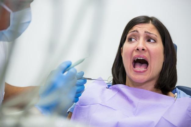Paziente femminile spaventato durante un controllo dentale