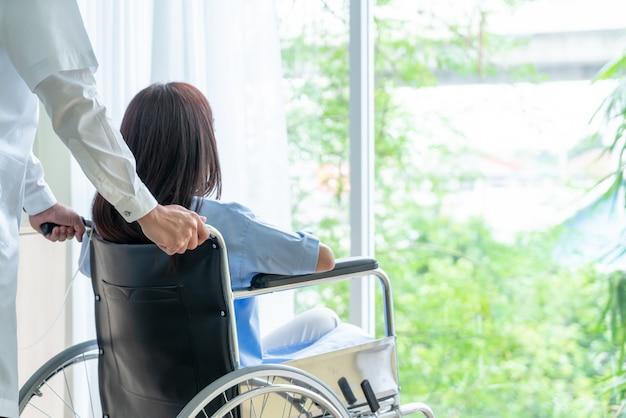 Paziente femminile su sedia a rotelle con medico senior