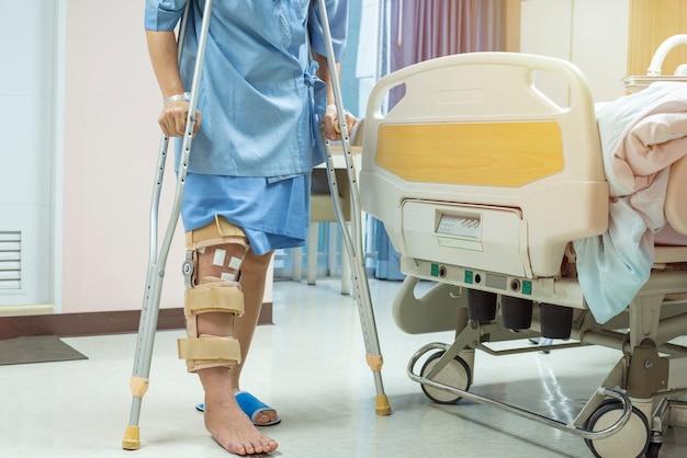 Paziente in piedi sulla stampella nel supporto di ginocchiera del reparto ospedaliero dopo la chirurgia del legamento crociato posteriore, fasciatura sul ginocchio di stampelle. concetto di assistenza sanitaria e medica.