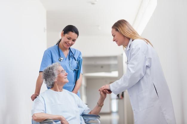 Paziente in una sedia a rotelle che tiene la mano di un medico