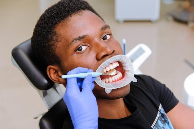 Paziente maschio africano che ottiene trattamento dentale in clinica dentale
