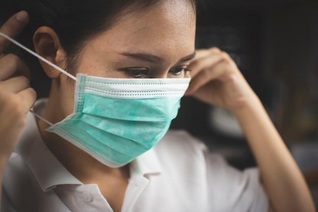 Paziente ragazza asiatica che indossa una maschera medica per prevenire le infezioni e prevenire la diffusione del coronavirus, prevenzione di covid-19.