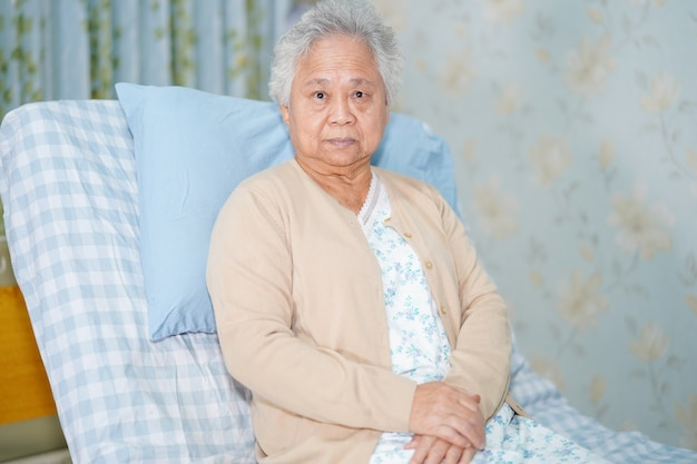 Paziente senior asiatico della donna che si siede sul letto in ospedale.