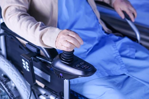 Paziente senior asiatico della donna di signora sulla sedia a rotelle elettrica all'ospedale di cura.