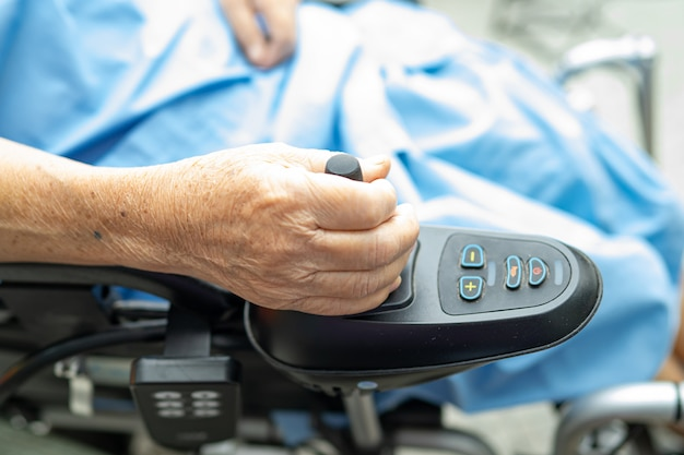 Paziente senior asiatico della donna sulla sedia a rotelle elettrica con telecomando all'ospedale.