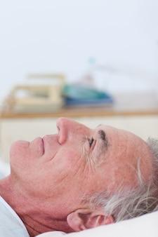 Paziente senior che si trova su un letto di ospedale