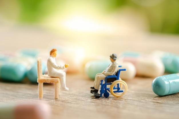 Paziente senior in sedia a rotelle che consulta medico, concetto medico di sanità.