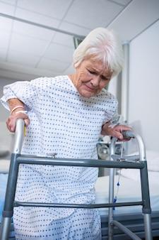 Paziente senior sorridente che tiene deambulatore per alzarsi