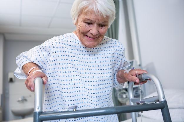 Paziente senior sorridente che tiene deambulatore