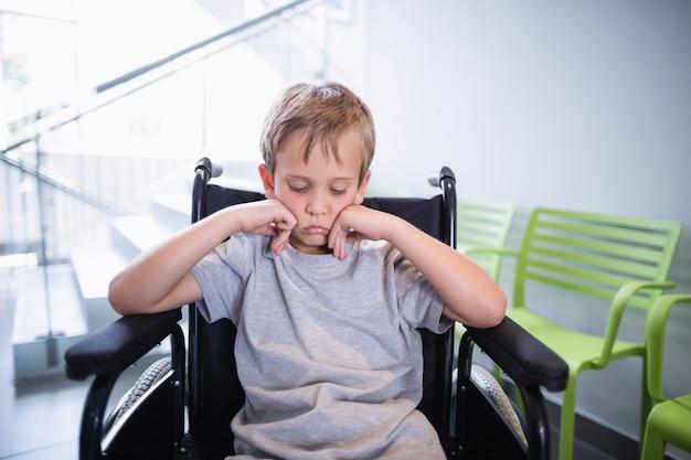 Paziente triste del ragazzo che si siede su una sedia a rotelle