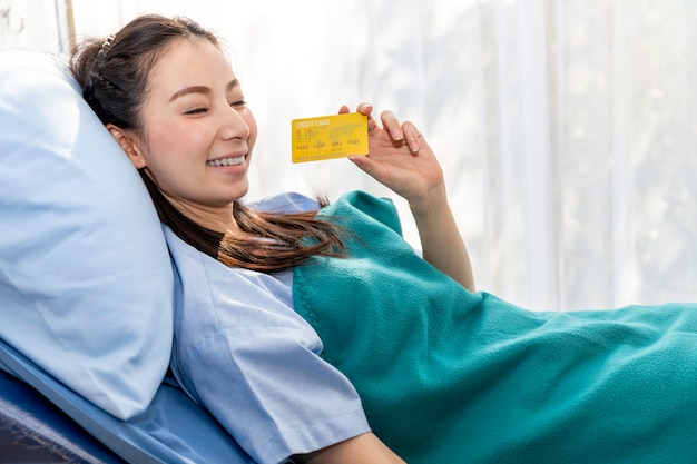 Pazienti asiatici che sorridono e che mostrano a disposizione una carta di credito dimostrativa.