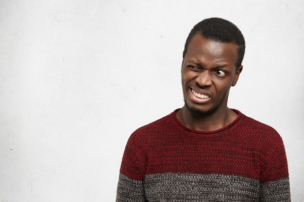 Pazzo divertente giovane afroamericano che indossa maglione casual in posa al chiuso facendo smorfie, facendo bocca, stringendo i denti e ammiccanti. espressioni facciali umane, emozioni e sentimenti