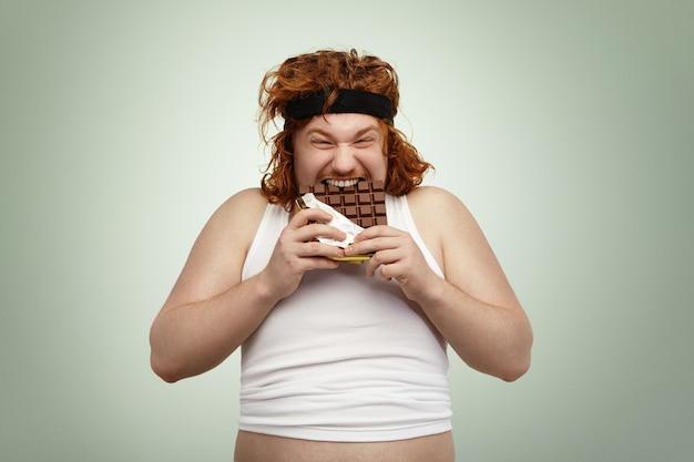 Pazzo e affamato giovane maschio europeo dai capelli rossi in sovrappeso con un buon appetito