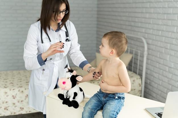 Pediatra medico che dà al bambino un'iniezione intramuscolare nel braccio