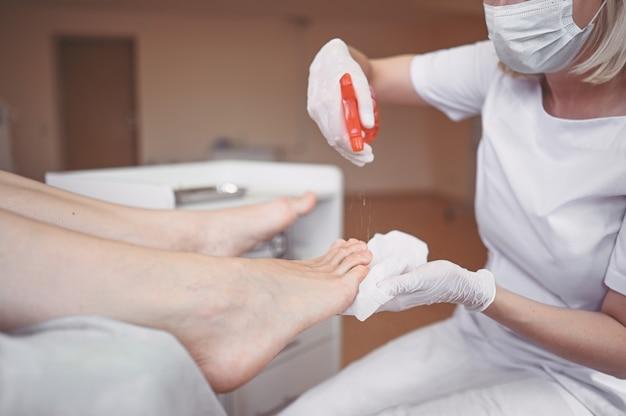 Pedicure che esegue la procedura professionale di pedicure medica nel salone di bellezza con eguipment speciale