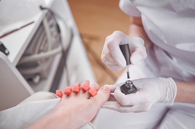 Pedicure che fa smalto bianco sulle gambe del cliente usando il separatore dito dito del piede