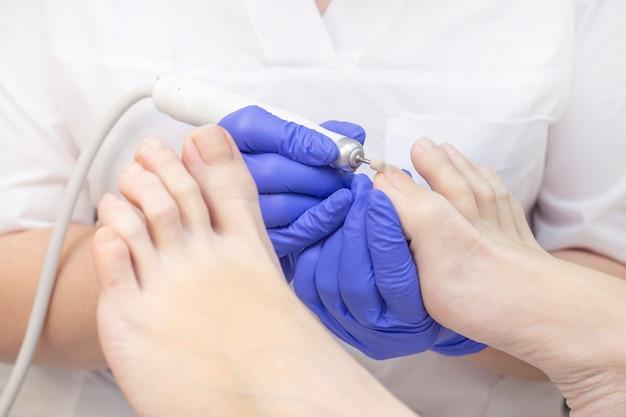 Pedicure terapeutica il podologo principale fa la pedicure hardware. visita alla podologia. trattamento ai piedi nella spa. clinica di podiatria.