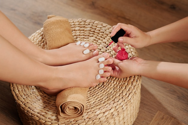 Pedicurist che applica smalto per unghie