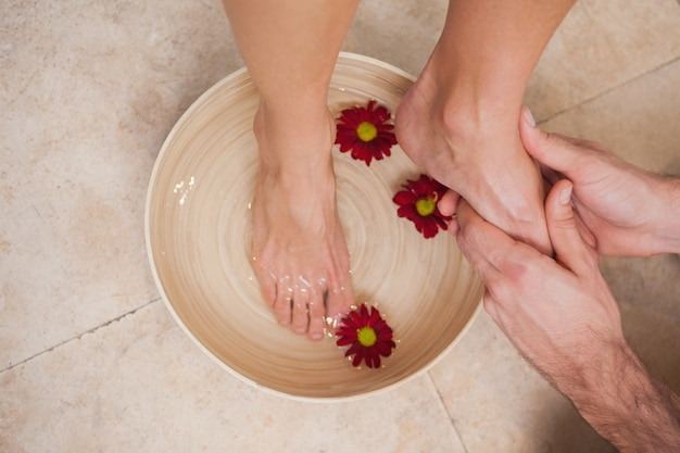 Pedicurista che lava i piedi ai clienti