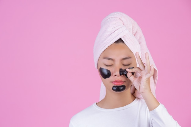 Peeling cosmetico di bellezza. giovane femmina con la maschera nera staccata sul prodotto cosmetico della sbucciatura di cura di pelle della pelle sul viso su un rosa.