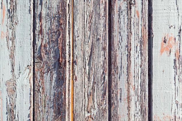 Peeling in legno a parete. vecchie tavole verticali verniciate. sfondo con texture.