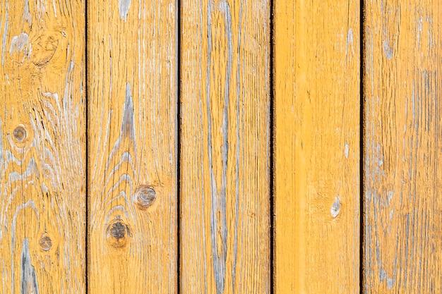 Peeling in legno giallo. vecchie tavole verticali verniciate. sfondo con texture.