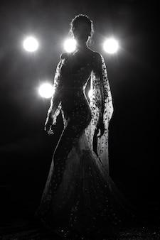 Pelle abbronzata asiatica slim donna sexy vede attraverso l'abito da sera con il fumo della luce posteriore