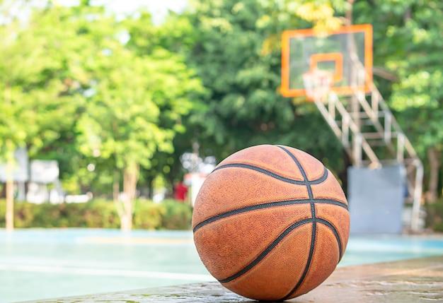 Pelle di pallacanestro sulla sedia di legno con gocce d'acqua