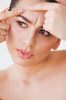 Pelle problematica. donna che schiaccia il punto sul viso e che osserva in specchio