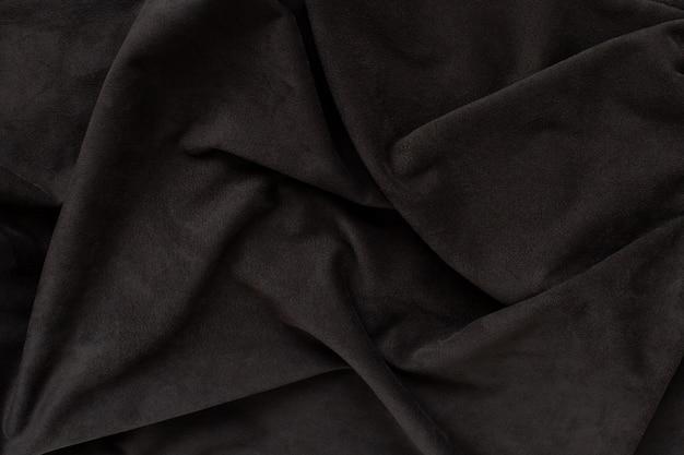 Pelle scamosciata marrone scuro con pieghe sulla superficie. trama di sfondo naturale